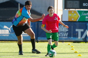 Nicole Christodoulou running with the ball at a soccer gala day