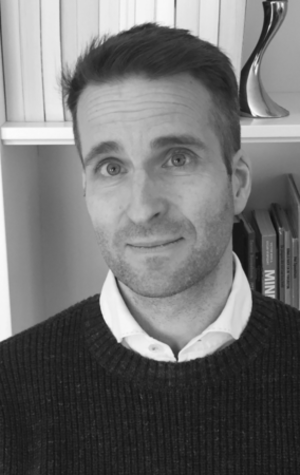Image of Olaf Verschuren. The photo is black and white and he is standing in front of a book shelf. Olaf is wearing a dark coloured sweater.
